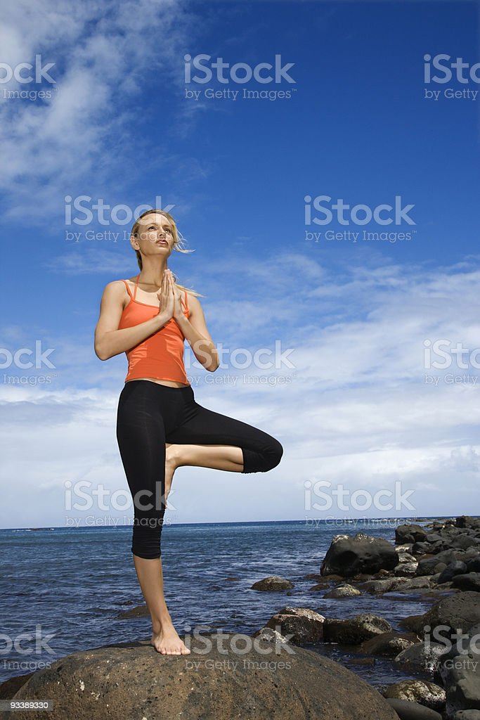 Woman doing yoga on rocky shore. royalty-free stock photo