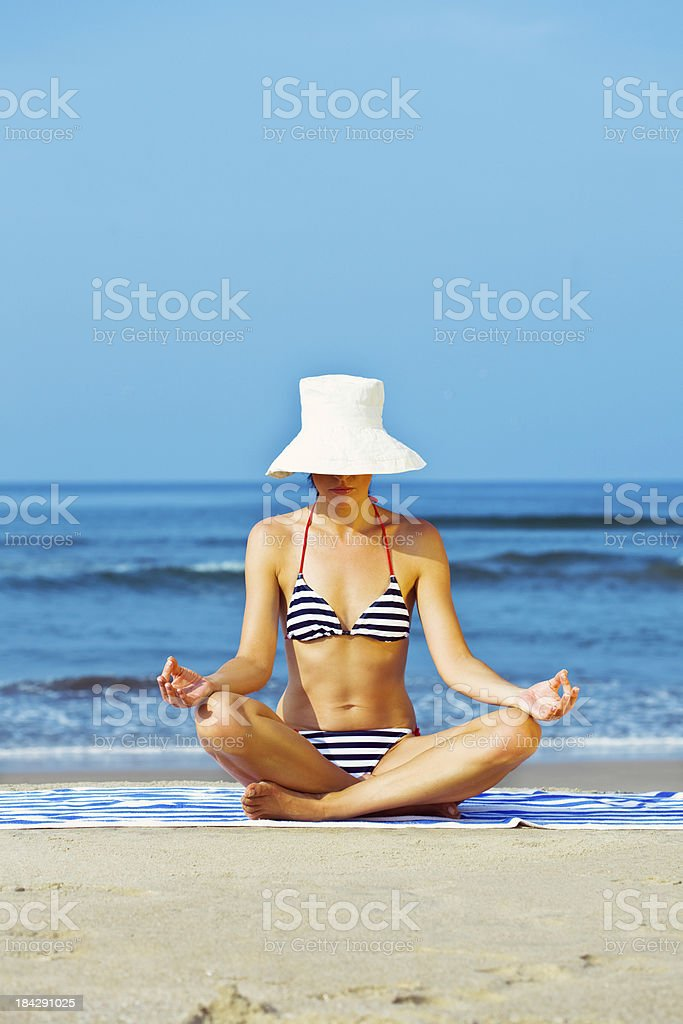 Woman doing yoga on the beach Woman wearing striped bikini and white summer hat sitting cross-legged on the beach and meditating. Blue ocean in the background. 25-29 Years Stock Photo