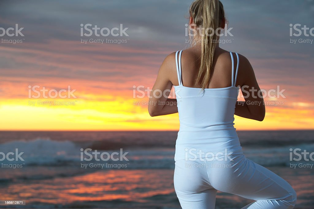 Woman doing yoga on the beach royalty-free stock photo