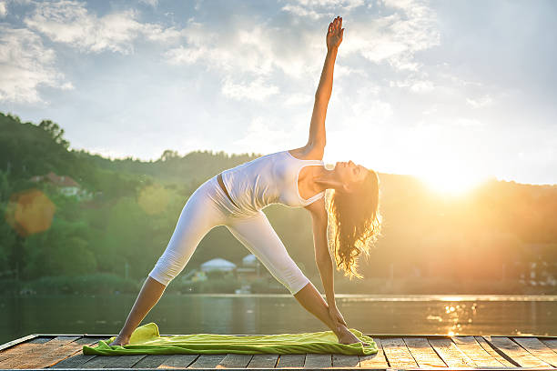 woman doing yoga on the lake - beautiful lights - yoga stock photos and pictures