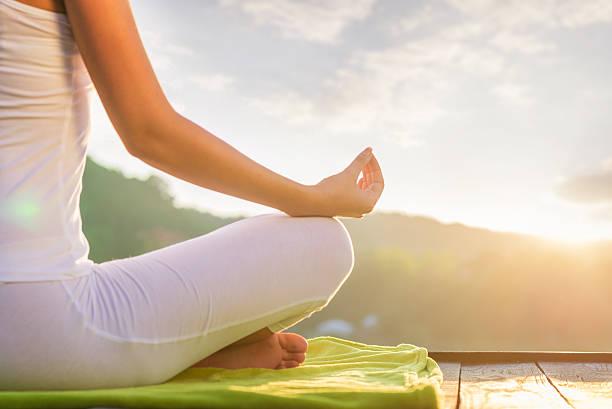 Woman doing yoga on the shore - half figure sitting stock photo