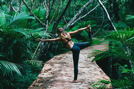 Young Caucasian woman doing yoga in the tropical forest