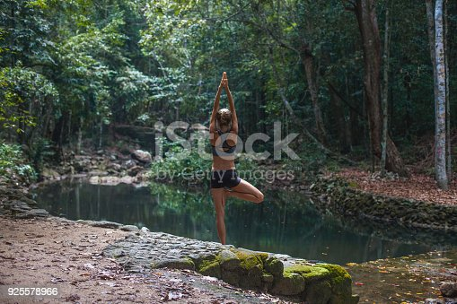 Woman doing yoga on tropical forest