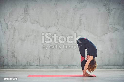Beautiful slim Caucasain brunette standing on the mat barefoot and doing Big Toe yoga pose.