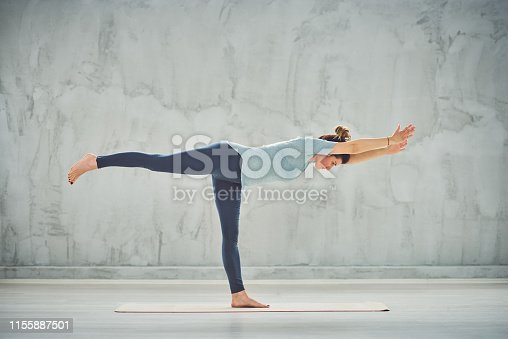 Side view of beautiful Caucasian woman standing on the mat in Warrior III yoga posture.