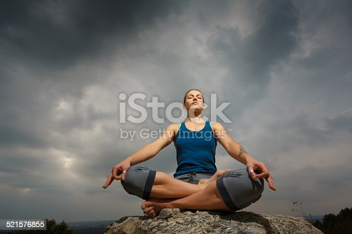 Woman doing yoga against the setting sun. Fitness classes outdoors. Stormy sky with sunshine.