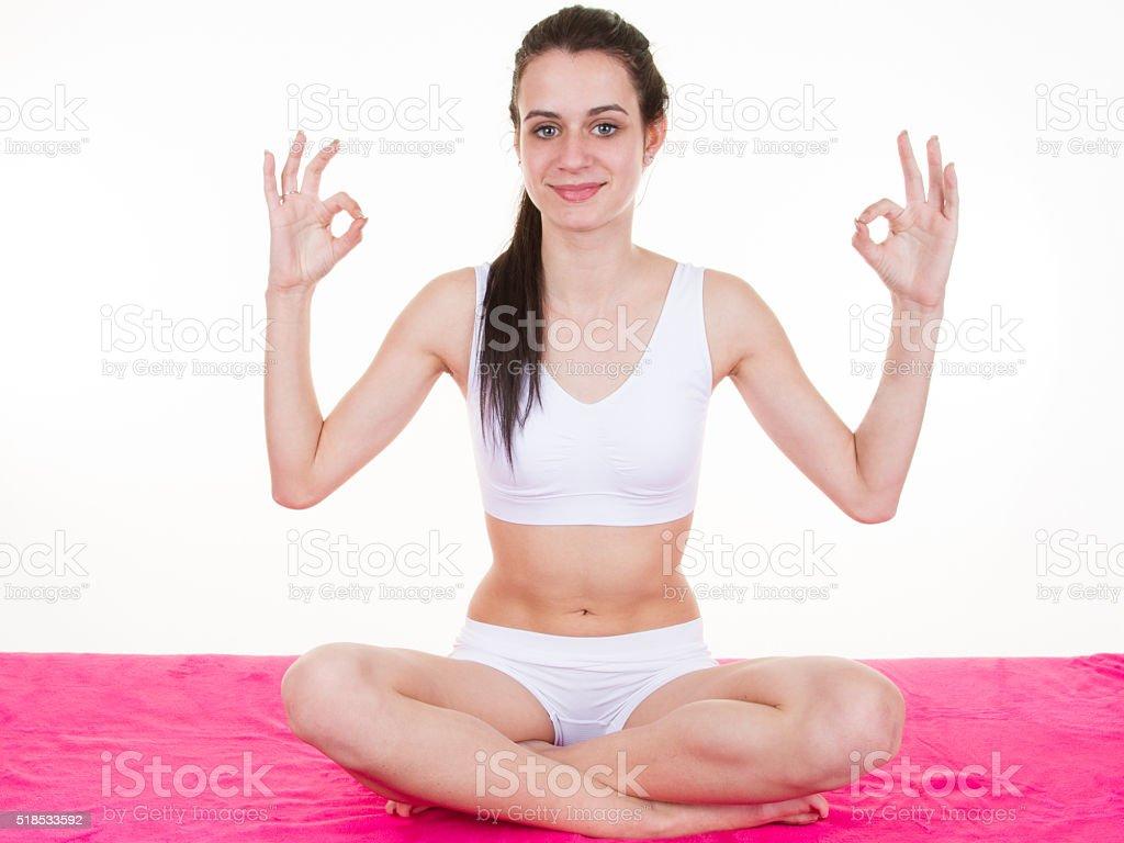 Woman doing yoga pose while sitting cross legged stock photo