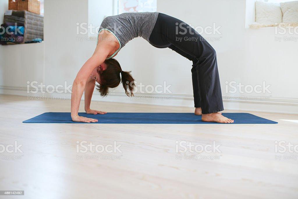 Woman doing yoga - Urdhva Dhanurasana pose stock photo