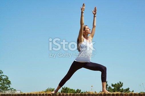 Woman training yoga against the blue sky