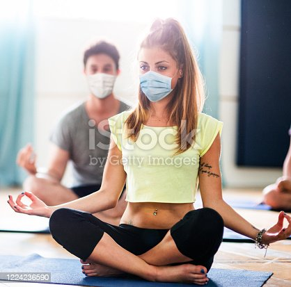 woman doing yoga with face mask
