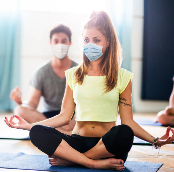 woman doing yoga with face mask stock photo