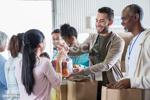 istock Woman donates bag of fruit to food bank 936497194