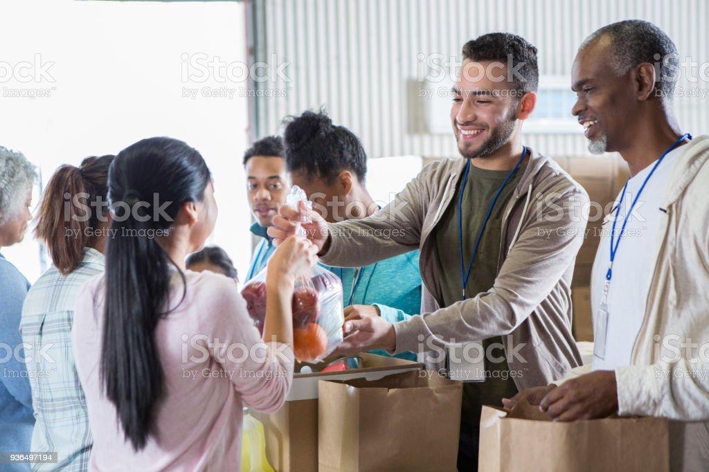 Woman donates bag of fruit to food bank stock photo