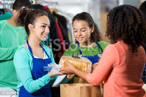 istock Woman donates bread loaf to food drive 513245674