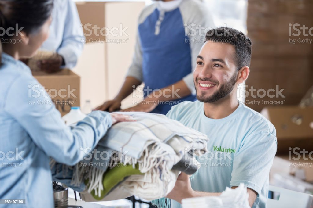 Woman donates warm clothing during clothing drive stock photo