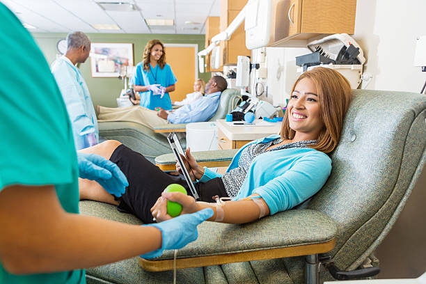 Woman donating blood in busy donation center stock photo