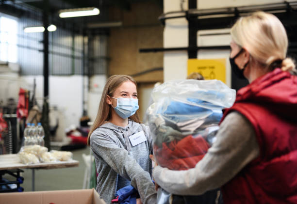 Woman donating clothes community charity donations center, coronavirus concept. stock photo