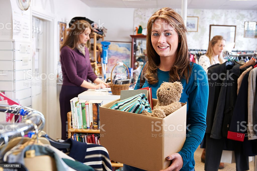 Woman Donating Unwanted Items To Charity Shop​​​ foto