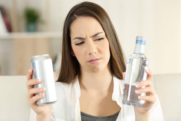 frau zweifeln zwischen wasser und soda trinken - wasser trinken abnehmen stock-fotos und bilder