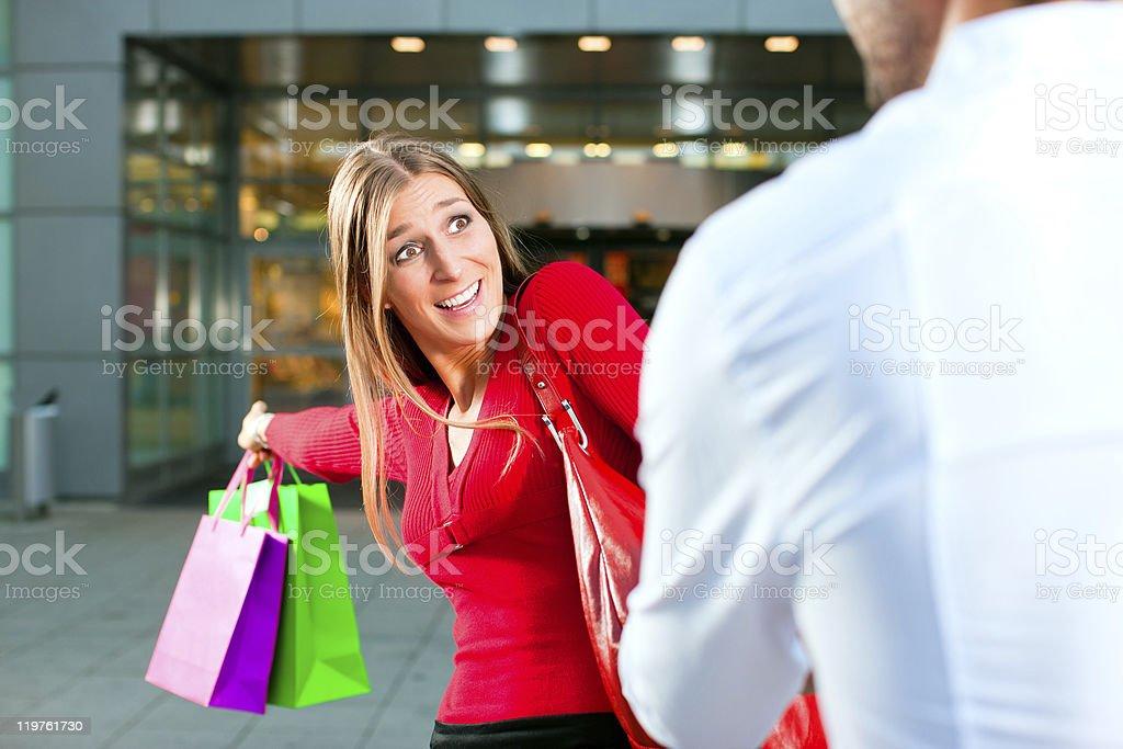 Woman dragging man into shopping mall stock photo