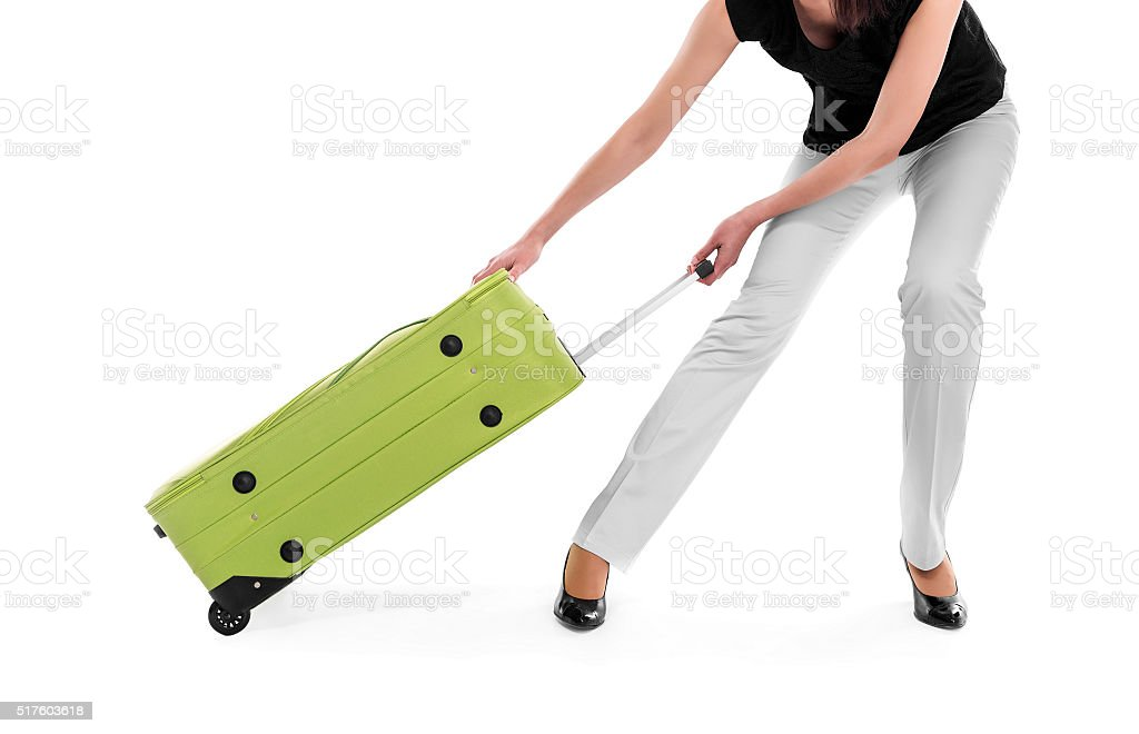 Woman drags a heavy suitcase stock photo