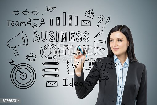 Portrait of woman with black hair who is drawing a business plan sketch on glassboard. Gray wall is in the background