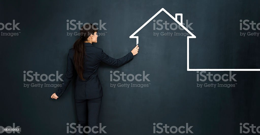 Woman drawing a house on big blackboard stock photo