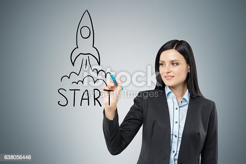 Black haired woman is drawing a launching rocket on glassboard. Gray wall is in the background
