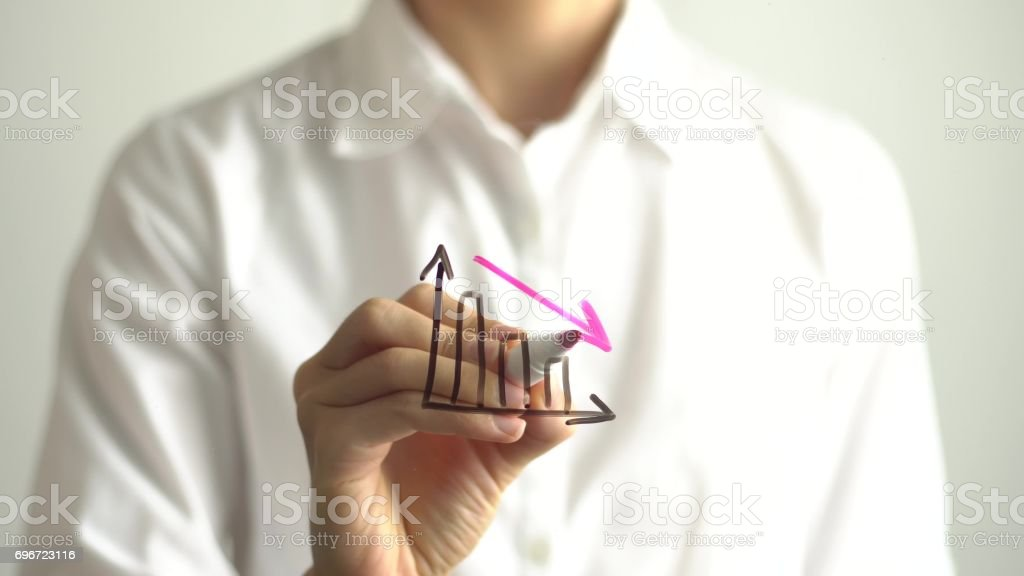 Woman drawing decrease diagram with red down arrow on transparent screen. stock photo