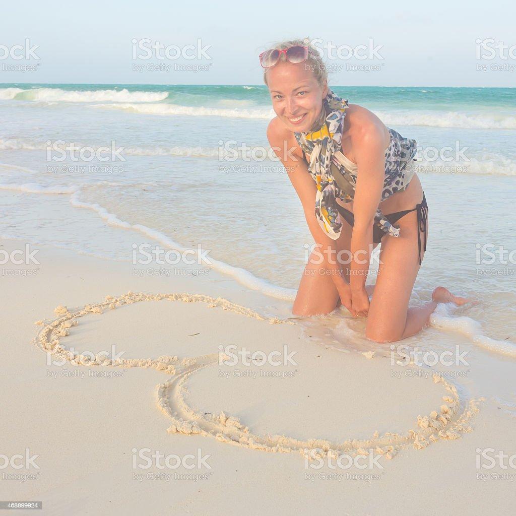 Frau Zeichnung Herz in den sand. Lizenzfreies stock-foto