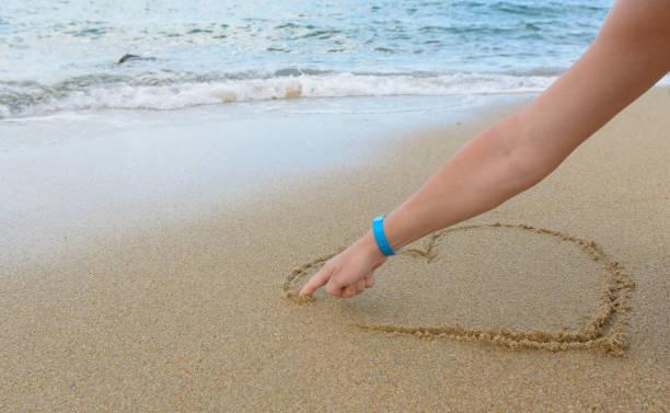 Frau Zeichnung Herzform in den sand – Foto