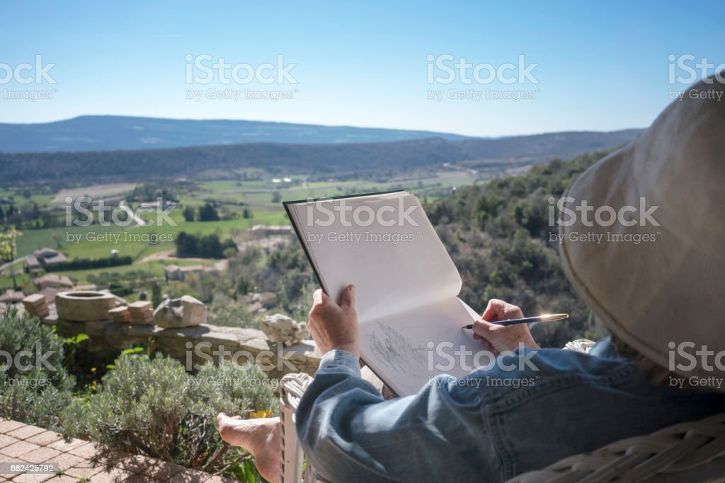 Woman drawing in a garden, overlooking a pastoral valley 免版稅 stock photo
