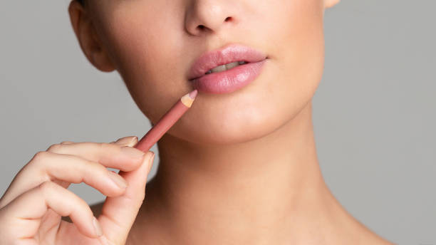 Woman drawing lips with nude pink lipliner Beauty concept. Woman drawing lips with nude pink lipliner over grey background, crop nude women pics stock pictures, royalty-free photos & images