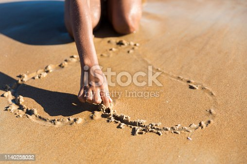Young woman drawing a heart shape with her hand on the sand. Sunny day at the beach