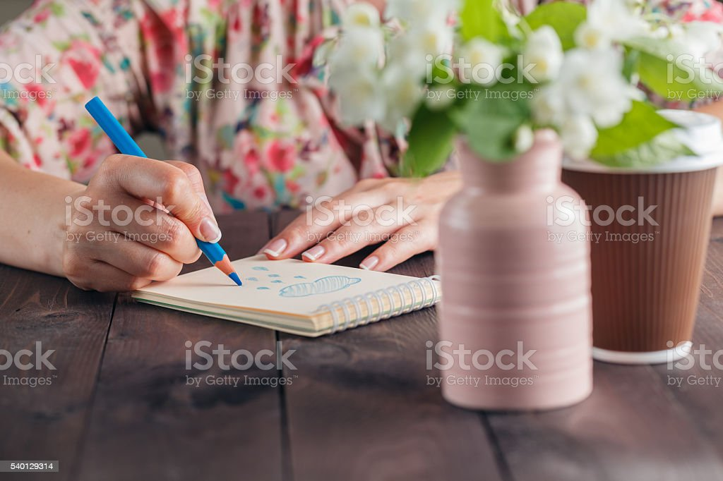 Woman drawing on notebook paper stock photo