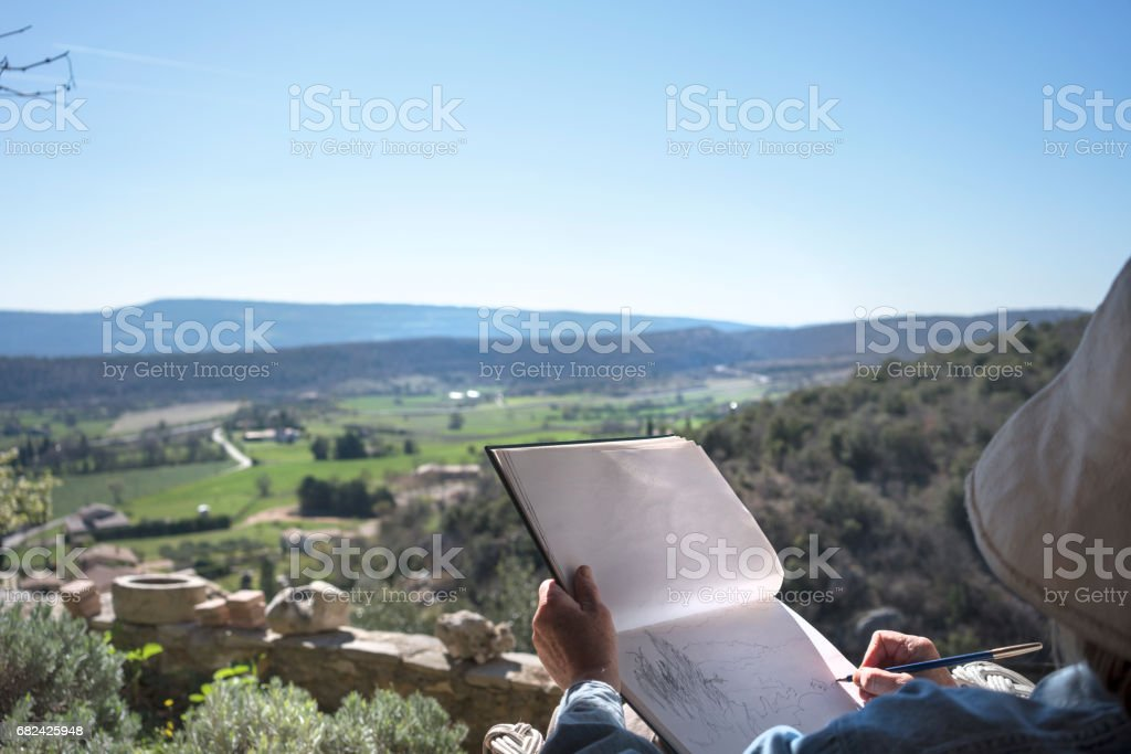 Woman drawing, overlooking a pastoral valley royalty-free stock photo