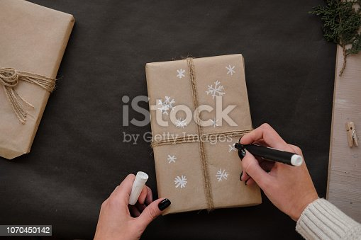 Woman drawing Snowflakes on paper package Christmas box Gift on black background. Female hands painting on Presents for winter Holidays. Christmas, New Year, shopping, preparation on Holidays concept