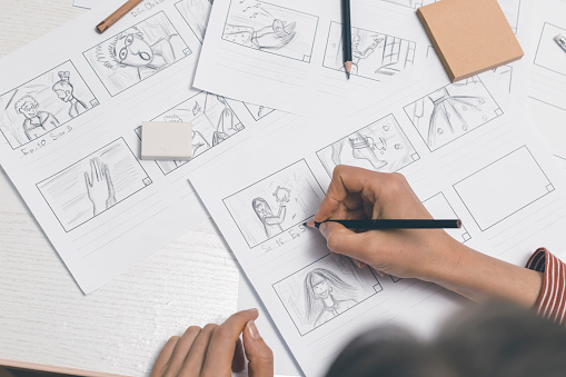 Woman draws storyboard sketches for comics or film.
