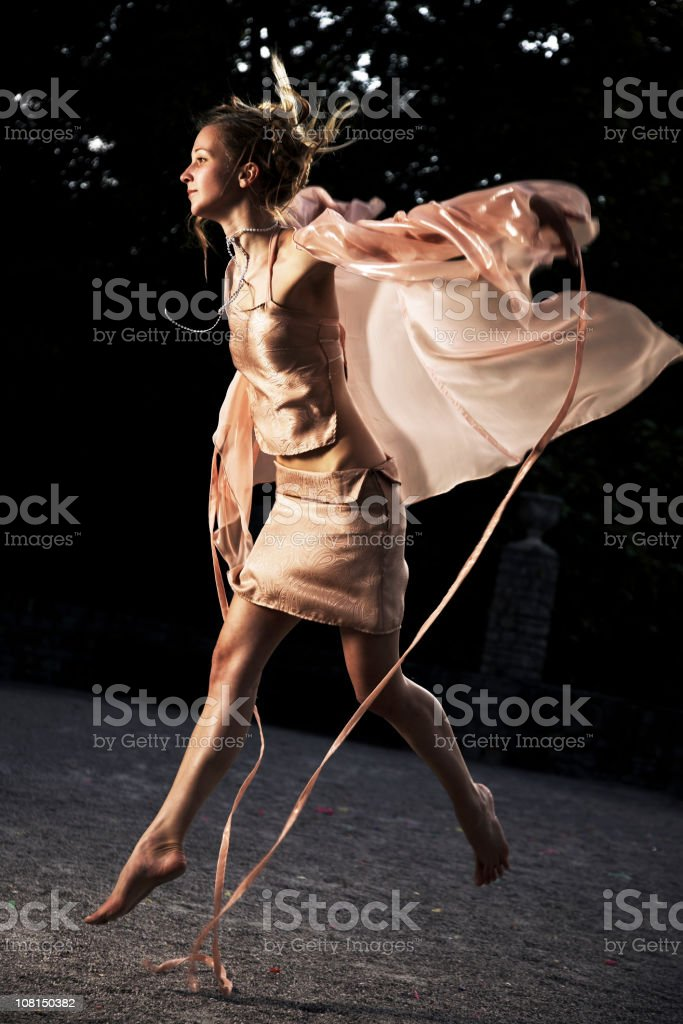 Woman Dressed as a Fairy and Jumping Outside in Courtyard royalty-free stock photo