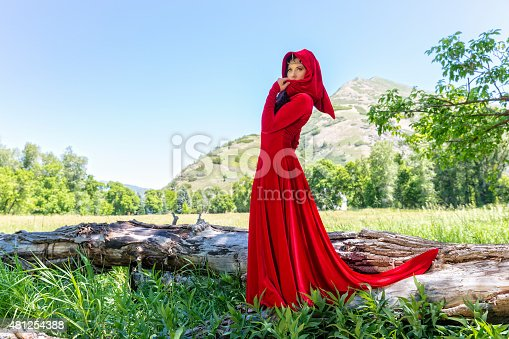 A beautiful Elf Princess is dressed in a red velvet dress with hood in an outdoor setting.