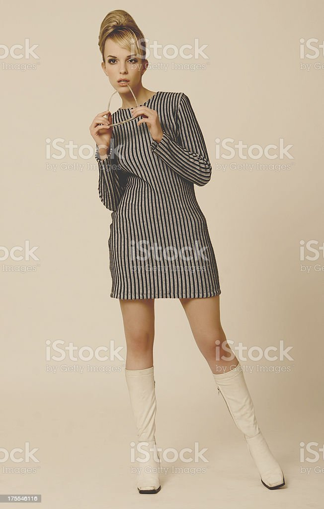Woman dressed in a 1960s striped mini dress and go-go boots stock photo