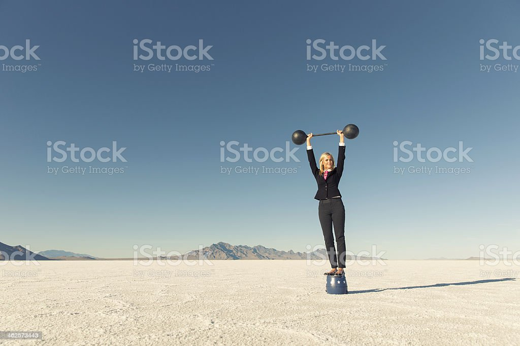 Woman Dressed in Business Suit Lifts Barbell on Salt Flats stock photo