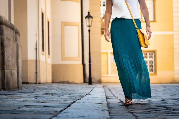 woman dressed in green pleated skirt is walking at old town. - spódnica zdjęcia i obrazy z banku zdjęć