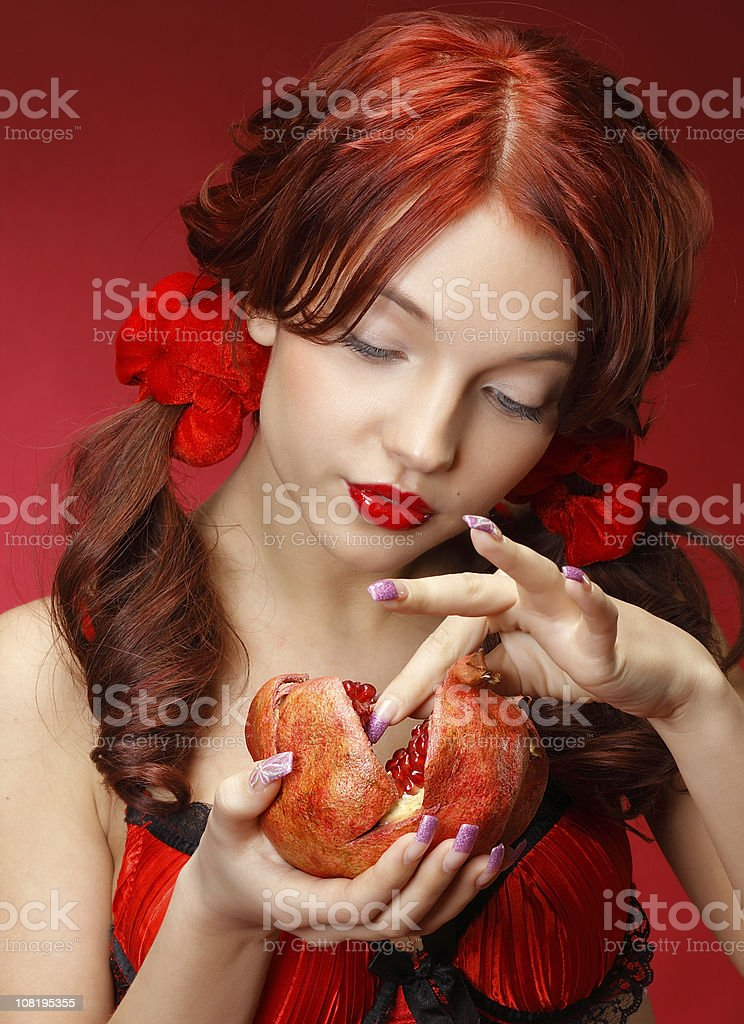 Woman Dressed in Red Holding Pomegranate Fruit royalty-free stock photo