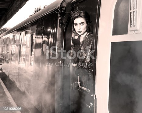 Attractive woman, female wearing vintage evening dress leaning out of window of steam train and blowing a kiss
