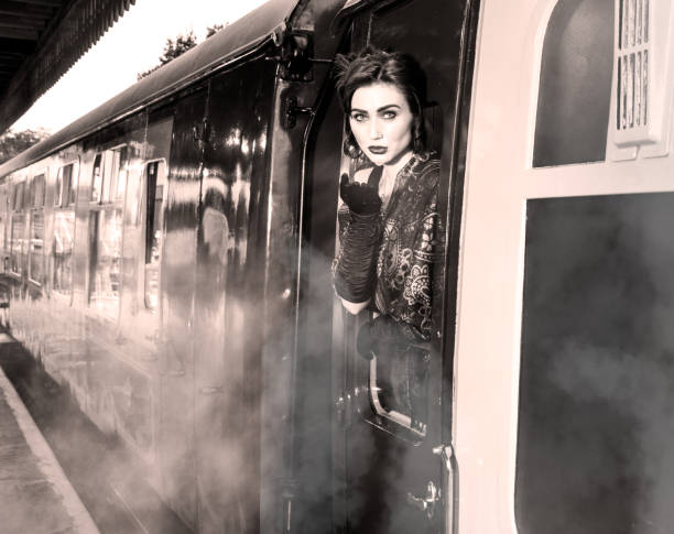 Woman dressed in vintage evening dress leaning out of train window and blowing a kiss stock photo