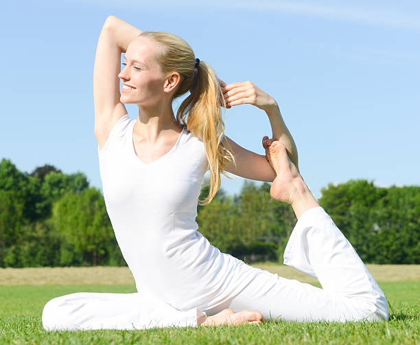 frau gekleidet in weiß tun yoga im freien auf grünem gras - kundalini yoga stock-fotos und bilder