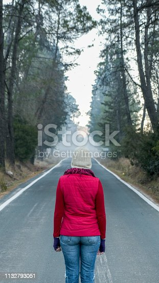 Rear view of a woman dressed in winter in the middle of a lonely road in a forest