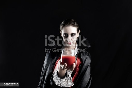 Studio shot in dramatic lights of a young female in dracula costume on black background