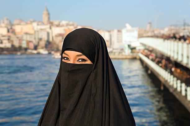 frau gekleidet in schwarz kopftuch, chador auf istanbul street t-shirt - burka stock-fotos und bilder